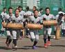 丸太を抱えて走るトレーニングに励む選手たち=和田大典撮影