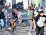イスラエル軍兵士(奥)に投石しながら逃げるパレスチナの若者ら=ベツレヘムで2017年12月10日、賀有勇撮影